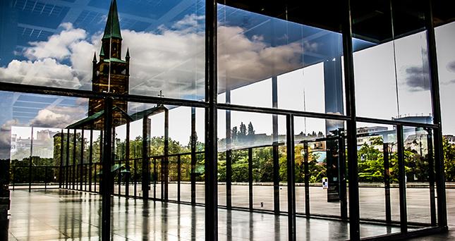 Die St. Matthäus Kirche spiegelt sich in den Fensterscheiben der Neuen Nationalgalerie in Berlin